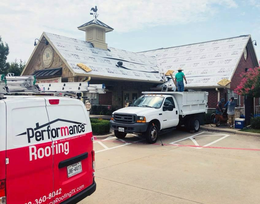 Performance Roofing van in front of a commercial roofing job in Collin County,TX