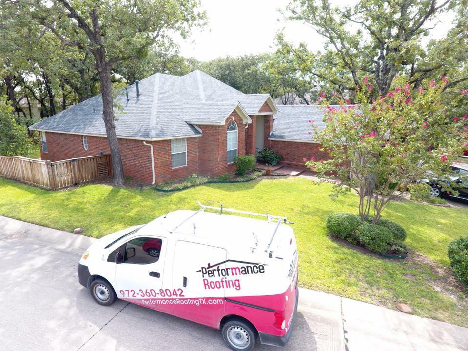 Performance Roofing van in front of a residential roofing job