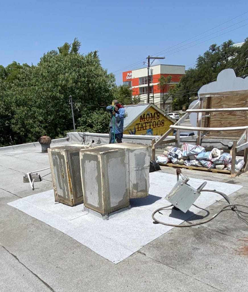 Workers on a roof, repairing a roof around AC units